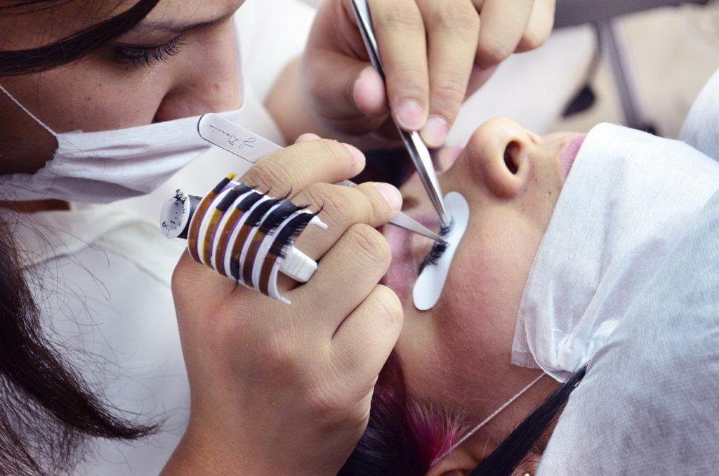 A technician performing eyelash extensions