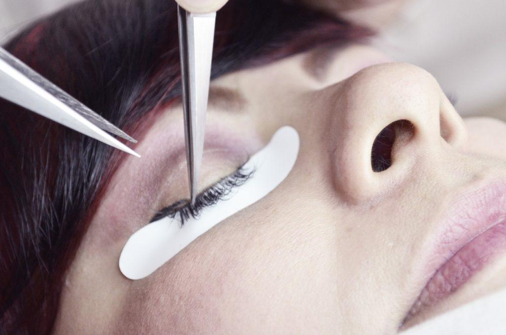 A close-up of eyelash extensions procedure