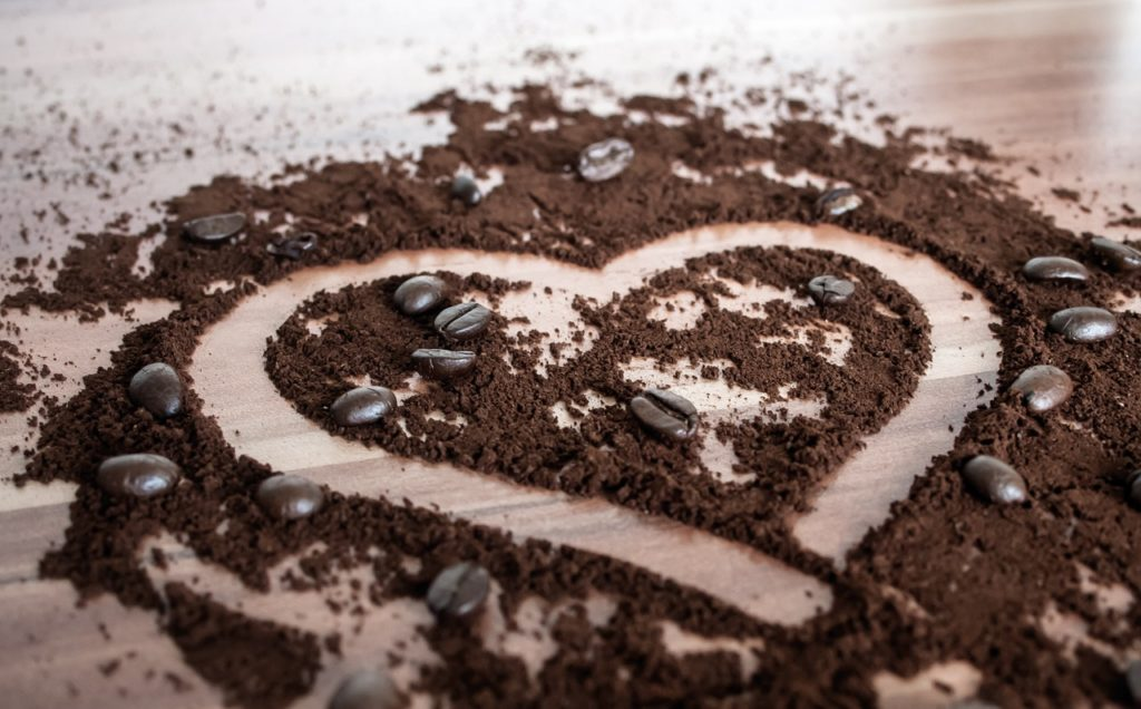 A heart drawn in coffee grounds and coffee beans