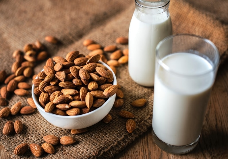 A glass of homemade almond milk next to a pile of almonds