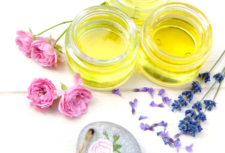 Three small glass containers full of jojoba oil