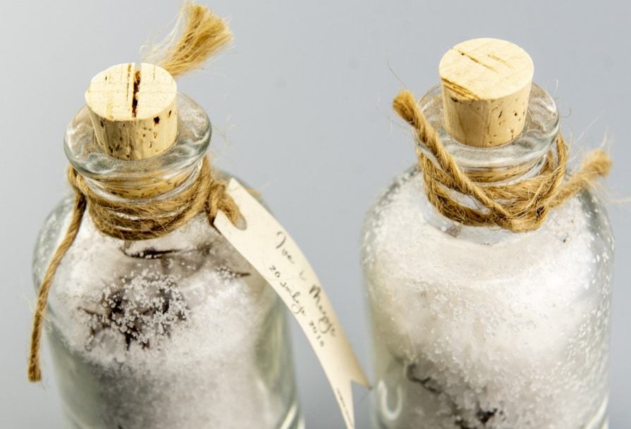 Two glass bottles filled with DIY salt scrub with lemon and sugar