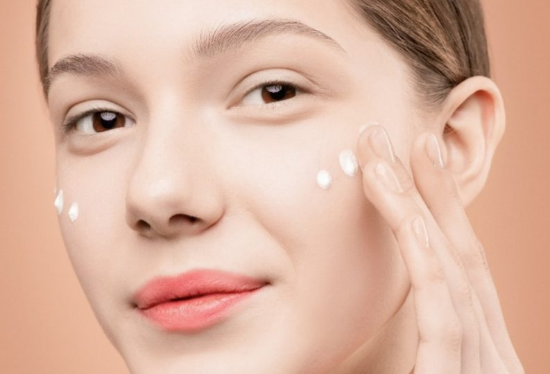 A girl applying acne spot treatment