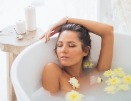 Sensitive skin symptoms and treatments - a woman soaking in a tub full of soothing mixture