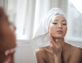 Retinol vs Retin-A - a girl in front of a mirror, using retinoid products.
