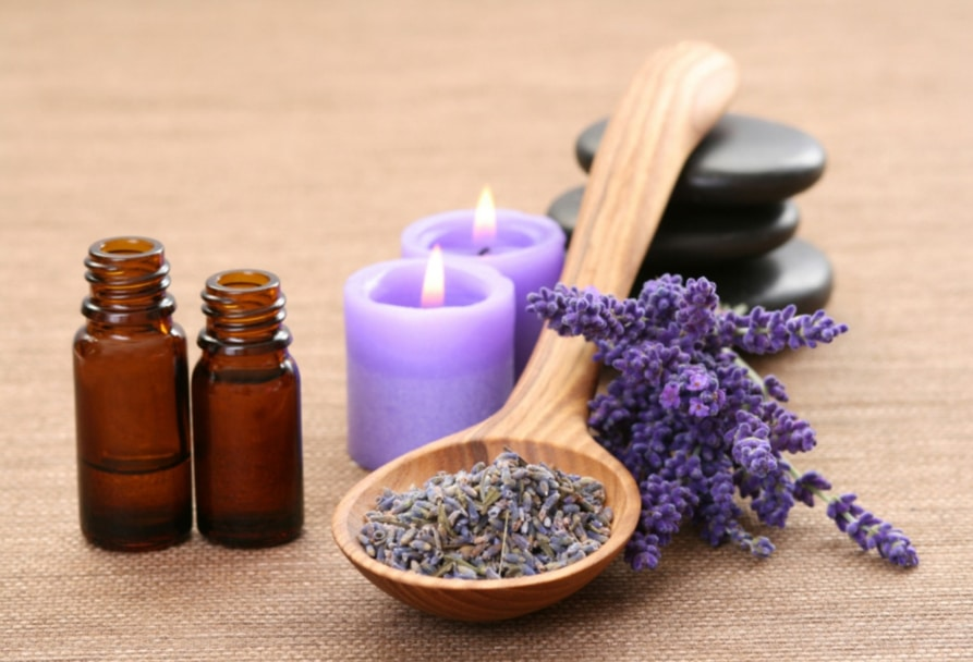 Two small bottles of lavender essential oil and a small pile of dried lavender
