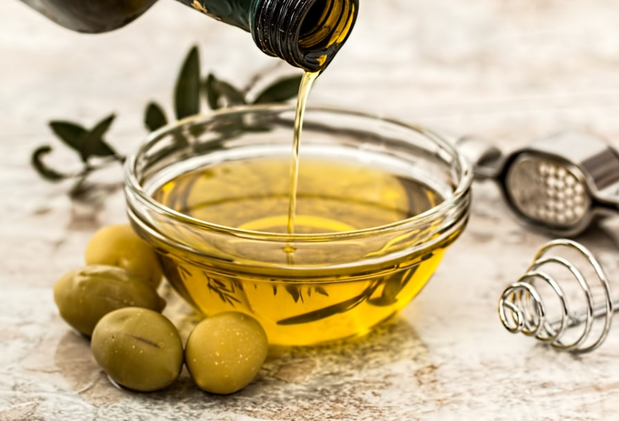 Olive oil in a small bowl surrounded with fresh olives