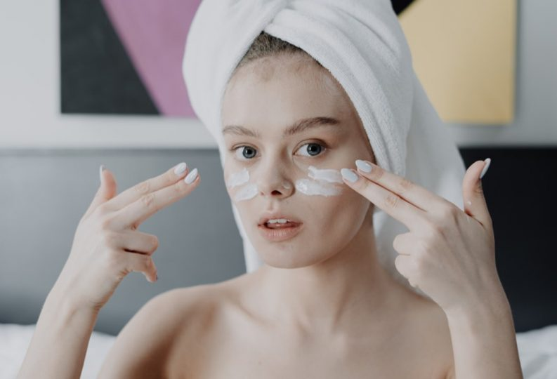 A girl applying petrolatum to her face as a part of the skin slugging technique