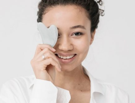 A girl doing a gua sha facial at home