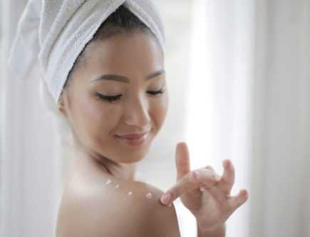 A girl applying one of the best body lotions for dry skin to her shoulder