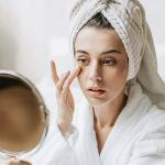 A girl in front of a mirror using products with the best anti-aging ingredients in skin care